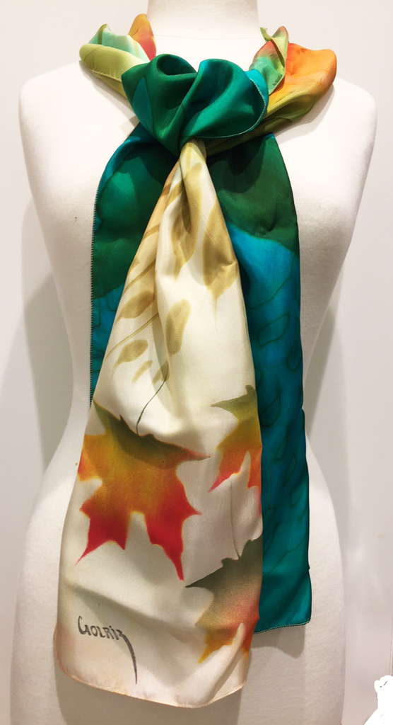 Pictured here is a green/teal/gold/ivory hand-painted silk scarf featuring several Canadian maple leaves of various sizes.