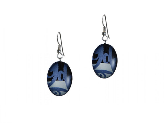 A pair of earrings featuring a piece of silk print by artist Corrine Hunt. The silk is patterned with blue, white and black, and is cut in an oval shape. The silk is encased in clear coat and hung on sterling silver hooks.