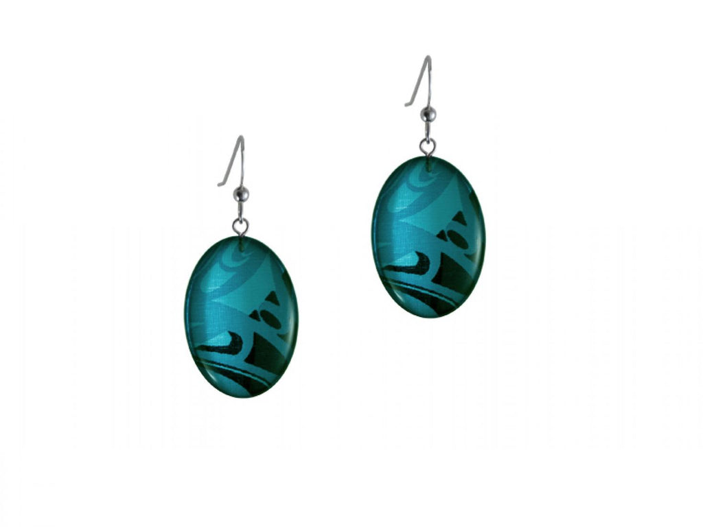 A pair of earrings featuring a piece of silk print by artist Corrine Hunt. The silk is patterned with black and two shades of turquoise, and is cut in an oval shape. The silk is encased in clear coat and hung on sterling silver hooks.