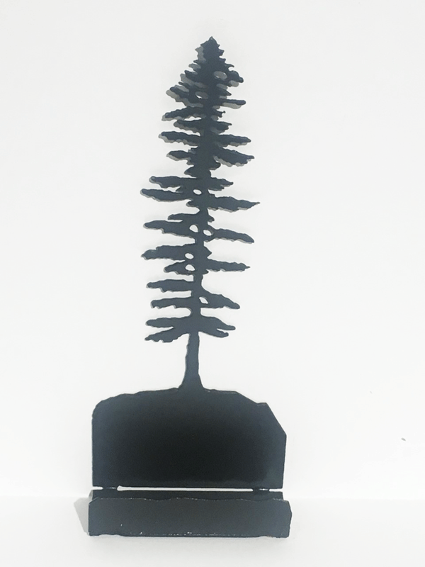This metal sculpture shows the matte black silhouette of a Sitka pine tree.  The Sitka tree is tall but slim. Its short, broad branches are about the same length along the whole tree, except at the top where they form a point. At the base of the tree is a small metal ledge meant to hold business cards.