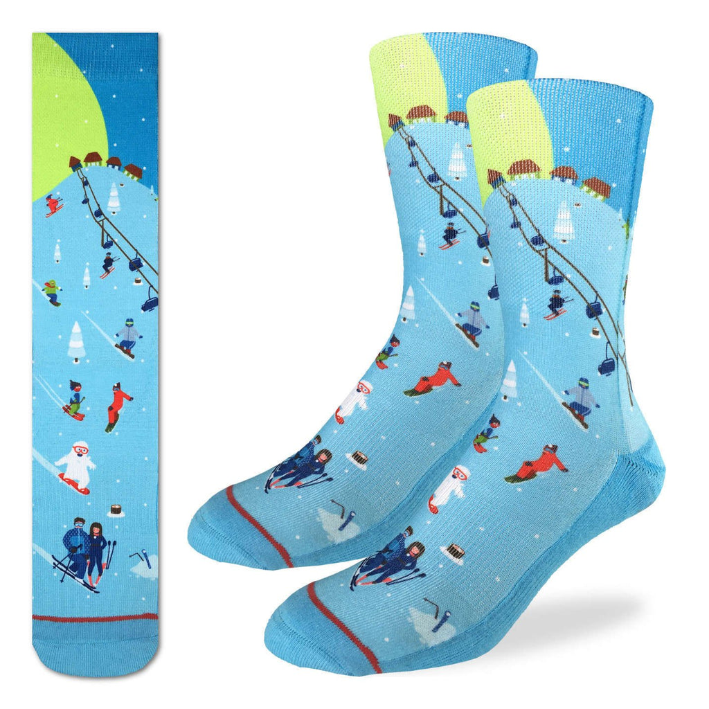 These fun socks feature a cartoon image of a ski slope with people riding a lift, people skiing or snowboarding down the hill, and some shacks at the top of the hill with snow covered pine trees dotted around the slope. The slope is coloured a light blue, while the sky behind is a darker blue with the moon and stars. The sole, toe, and heel of the socks are a darker blue, same as the sky. The active fit socks sport elastic arch bands to contour to your feet and provide support.