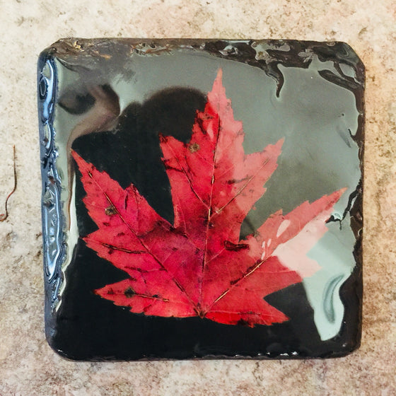 A square piece of slate featuring a single red maple leaf