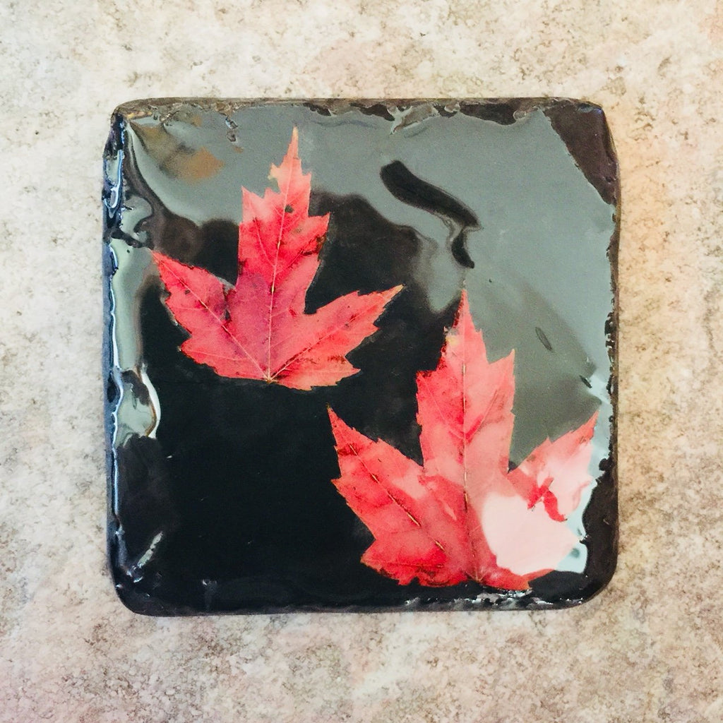 A square black piece of slate featuring two red maple leaves.