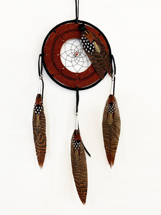 This dream catcher features a ring of rust coloured leather with a pattern of lines and dots branded onto it. A hole in the center of the leather is filled with string woven in a spiral pattern. A small stone sits in the center. Black, and brown speckled feathers lay across the leather ring on the top right, and hang from three leather strings along the bottom.