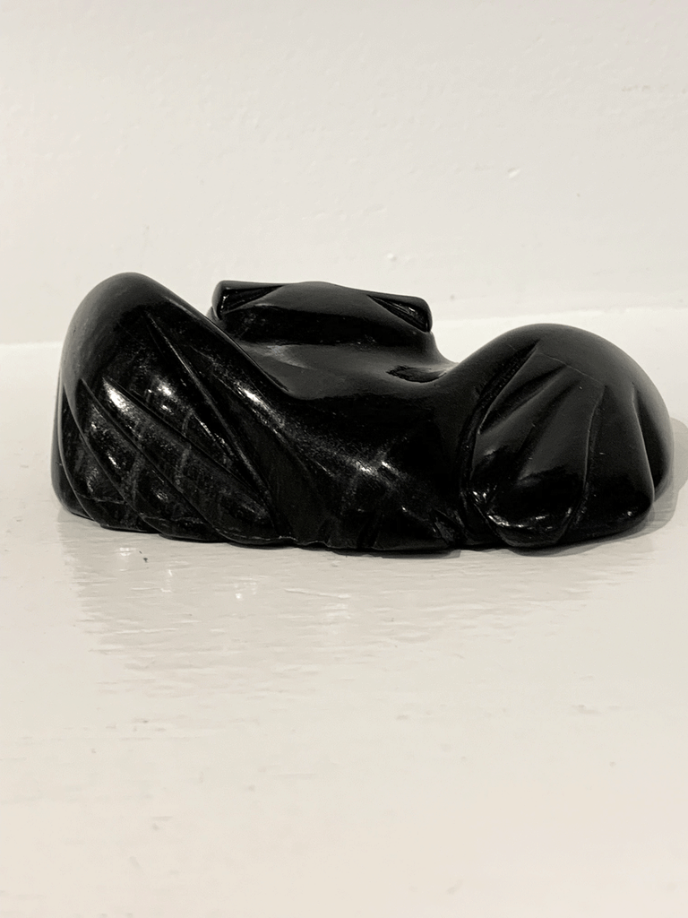 "A soapstone carving of a ""pancake owl"" ( title due to the sculpture's flat quality) by Joanasie Manning. This piece is made from dark black stone with some marbled grey patterning throughout. In this photograph, a back view of the owl is sho`wn."