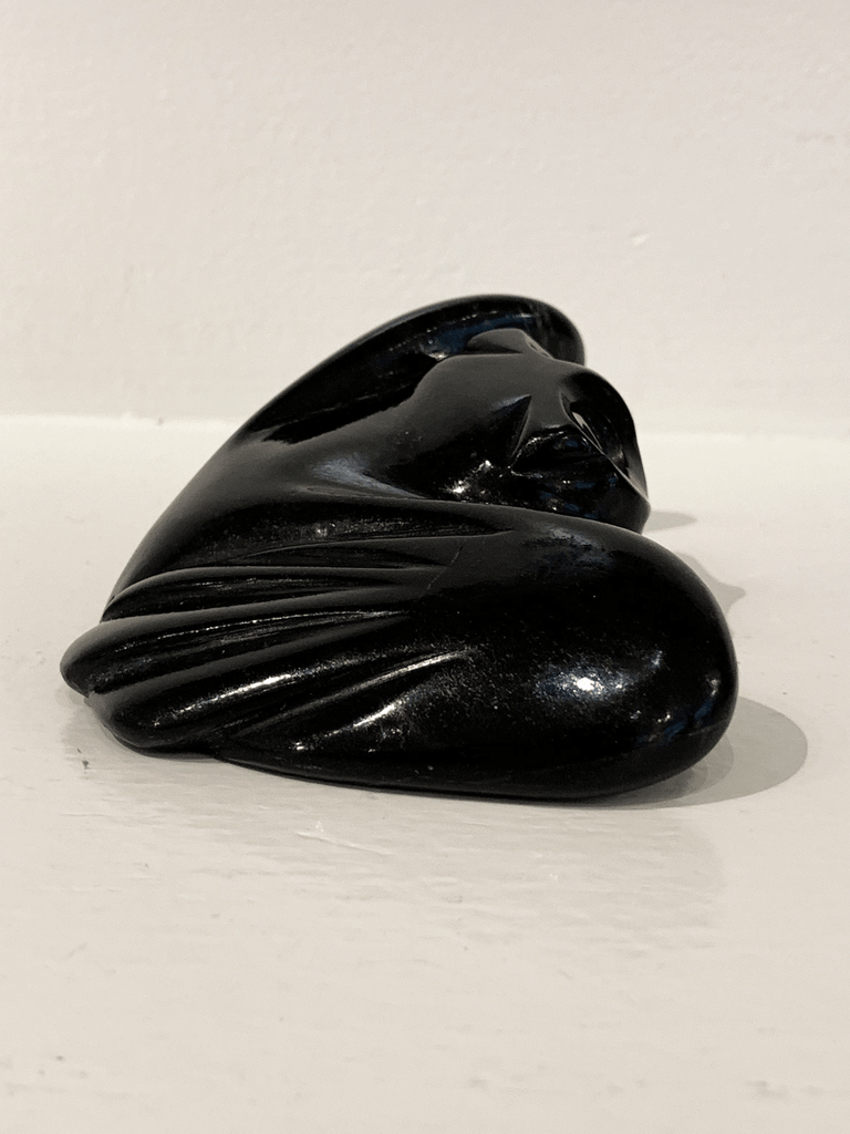 "A soapstone carving of a ""pancake owl"" ( title due to the sculpture's flat quality) by Joanasie Manning. This piece is made from dark black stone with some marbled grey patterning throughout. In this photograph, a side view of the owl is shown."
