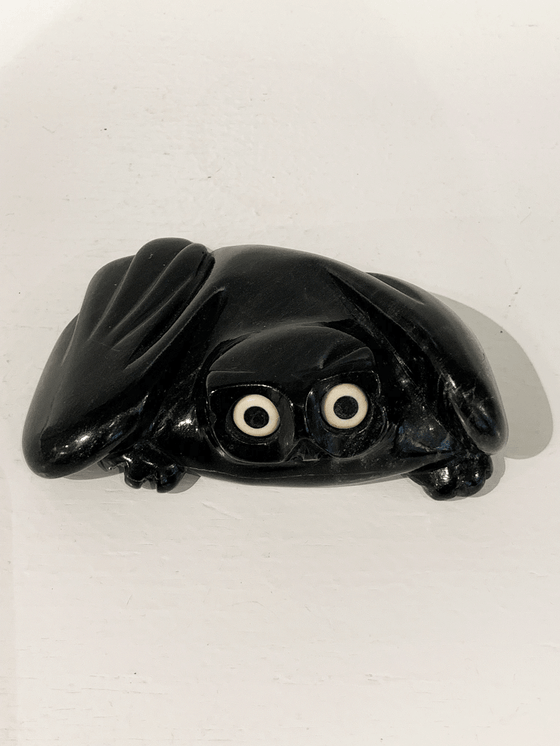 "A soapstone carving of a ""pancake owl"" ( title due to the sculpture's flat quality) by Joanasie Manning. This piece is made from dark black stone with some marbled grey patterning throughout. In this photograph, a front view of the owl is shown."