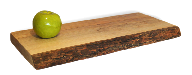 A board cut from a single piece of ambrosia maple. The board is approximately 20 inches long, 8 inches wide and 2 inches thick. The front-most edge is raw edged, and shows the original dark brown bark from the tree.