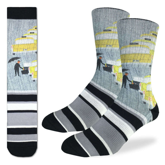 These fun socks feature a man in a suit with a briefcase and holding an umbrella about to enter one of the five yellow taxi cabs lined up one in front of the other. The background of the image is grey, and the image is printed twice on each sockmirriored on the vertical. Below the image white, grey, and black stripes in asymmetrical pattern to the end of the toe. The heel and rim of the sock are black. The active fit socks sport elastic arch bands to contour to your feet and provide support.