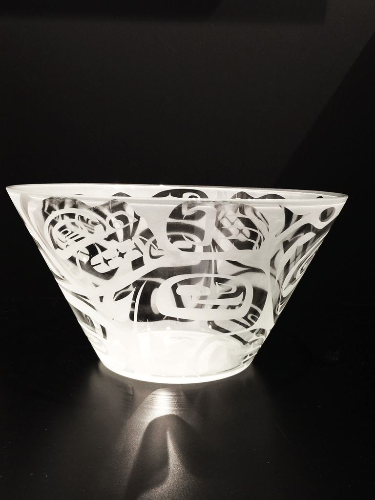 A side view of a glass bowl etched with a Haida bear design. This view emphasizes the straight sides of the bowl which taper from the wide lip of the bowl to its narrow base.