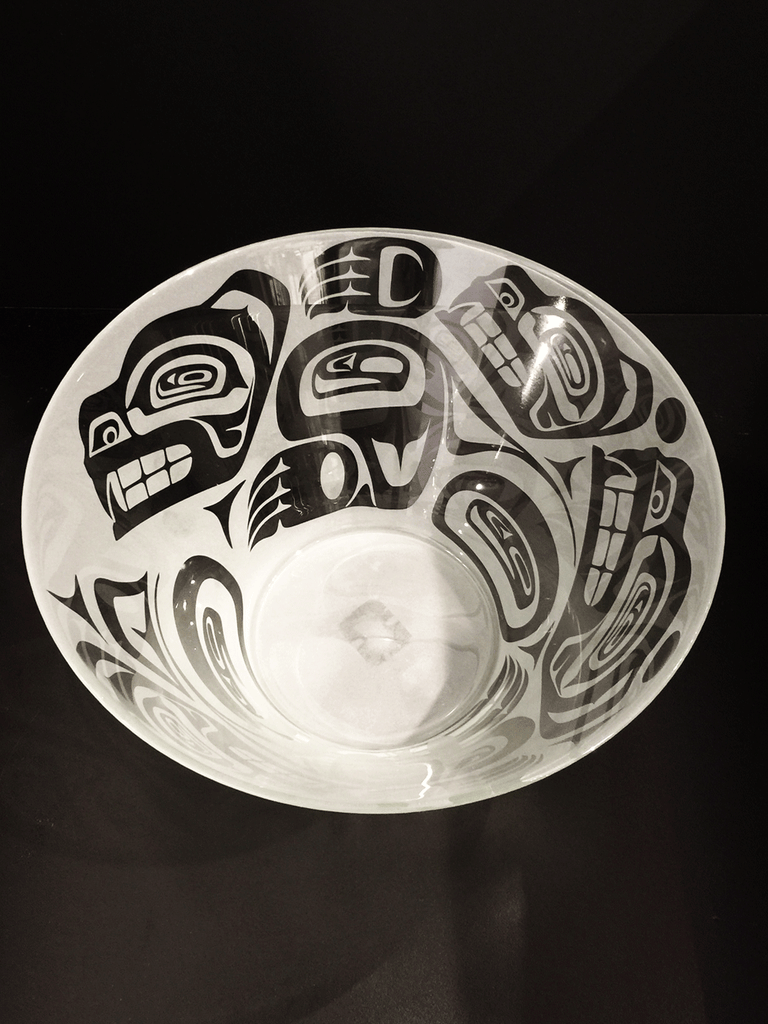 A top down of a glass bowl etched with a Haida design. This bowl features pack of bears running together. They clamber over each other in their excitement, partially obscuring some members of the group. The bears are clear, polished glass, while the surrounding space is frosted white.