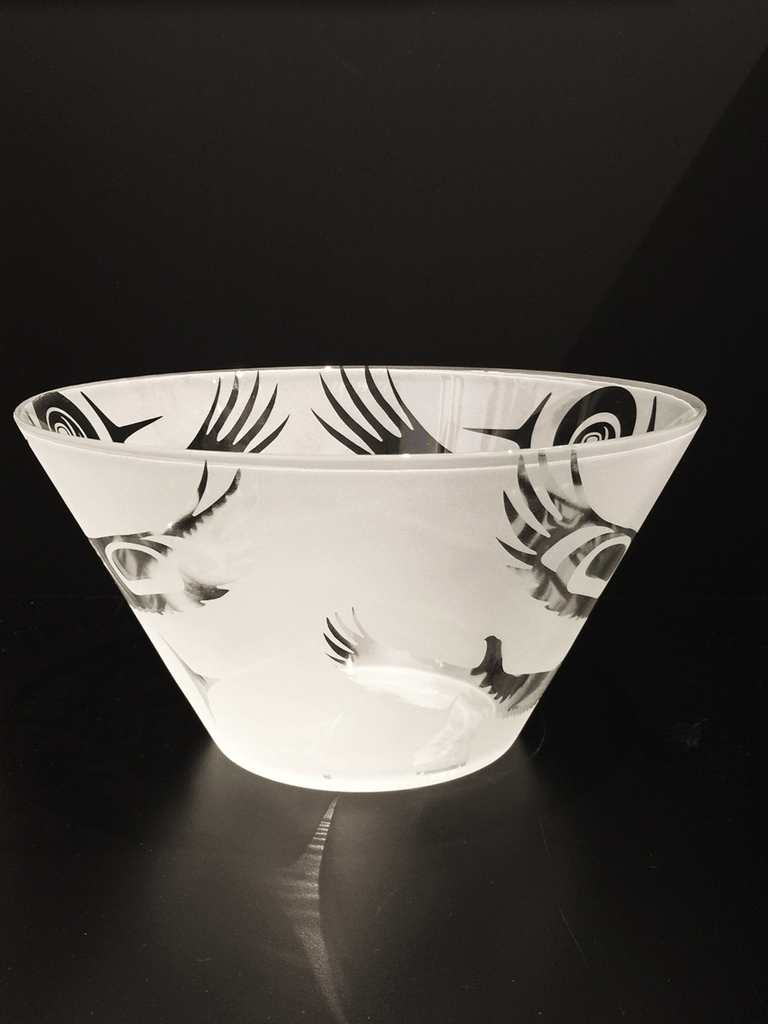 A side view of a glass bowl etched with a Haida eagle design. This view emphasizes the straight sides of the bowl which taper from the wide lip of the bowl to its narrow base.