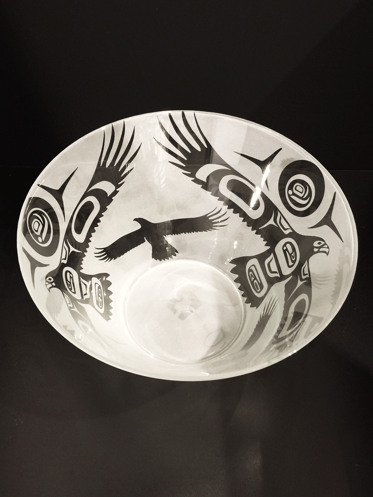 A top down of a glass bowl etched with a Haida design. This bowl features eagles soaring up toward an intense sun. Haida trigons form the strong rays of the sun as well as the wind that lifts the eagles' wings. The eagles are clear, polished glass, while the surrounding space is frosted white.