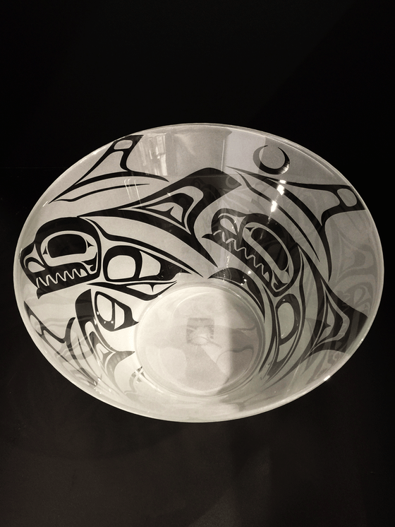 A top down view of a glass bowl etched with a Haida design. This bowl features a pod of orcas breaching from the waves under the light of the moon. The orcas are clear, polished glass, while the surrounding space is frosted white.