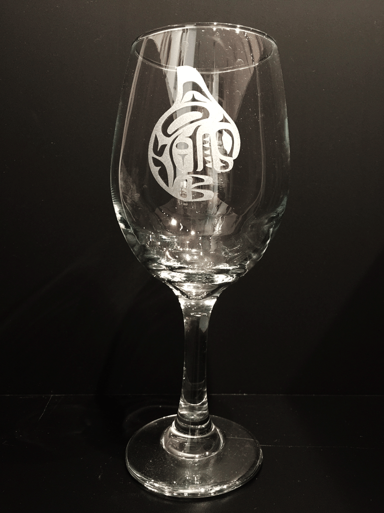 A long stem wine glass etched with a Haida orca design. The orca is curled in on itself, head and tail down but back fin high in the air, as if about to dive. The etching renders the orca in frosted white against the clear glass.