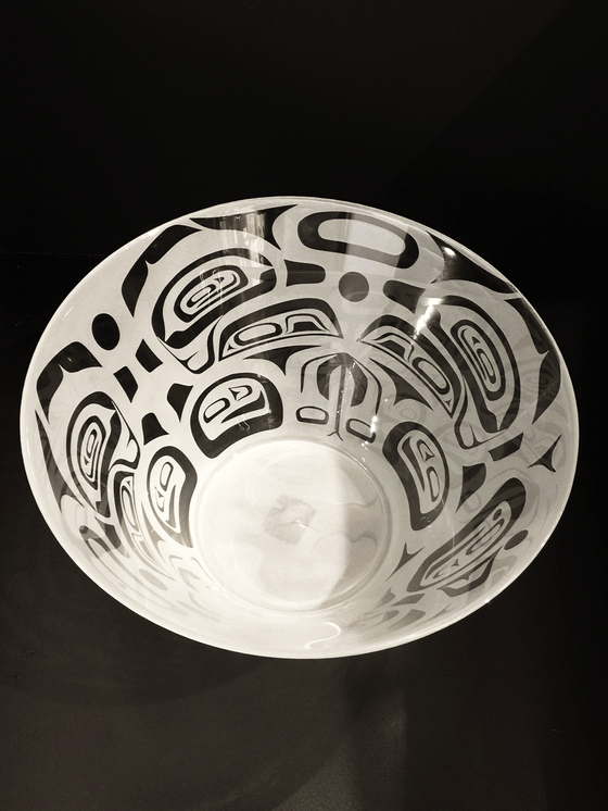 A top down of a glass bowl etched with a Haida design. This bowl features a complex series of forms that suggests feathers, claws, and beak of a raven. The repeating symmetrical design has a feeling of controlled chaos. The raven forms are clear, polished glass, while the surrounding space is frosted white.