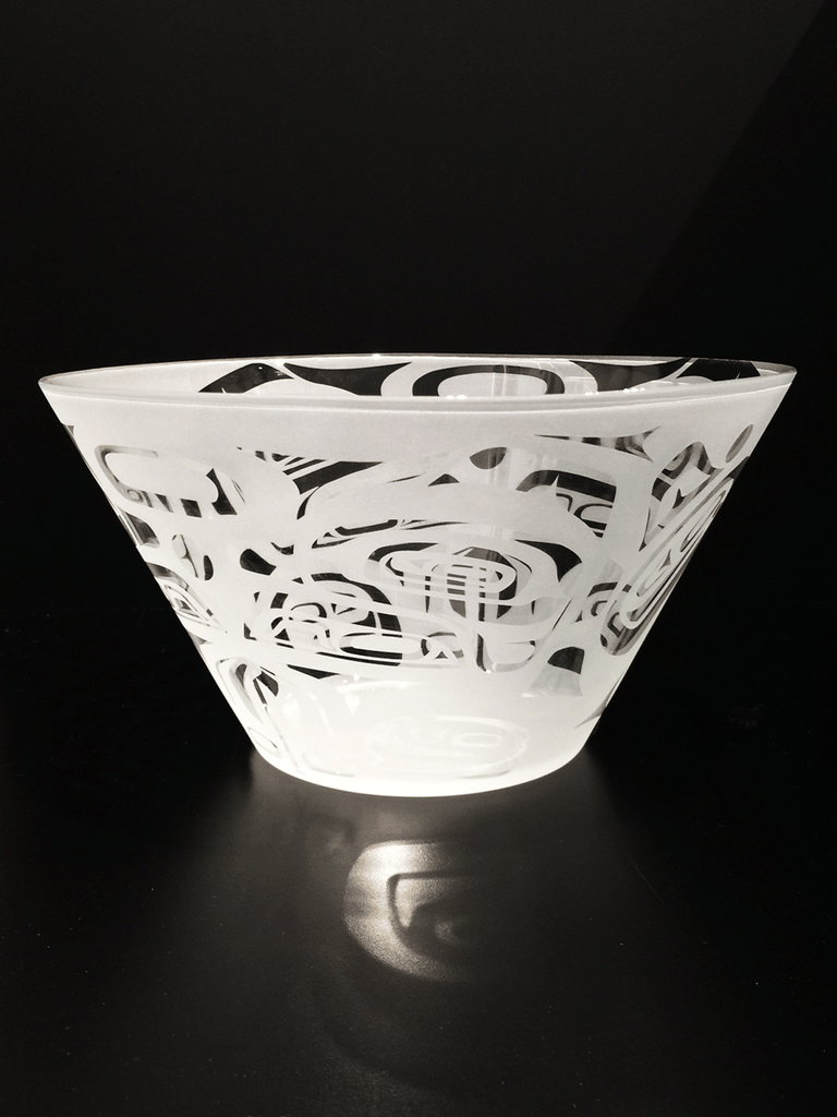 A side view of a glass bowl etched with a Haida raven design. This view emphasizes the straight sides of the bowl which taper from the wide lip of the bowl to its narrow base.