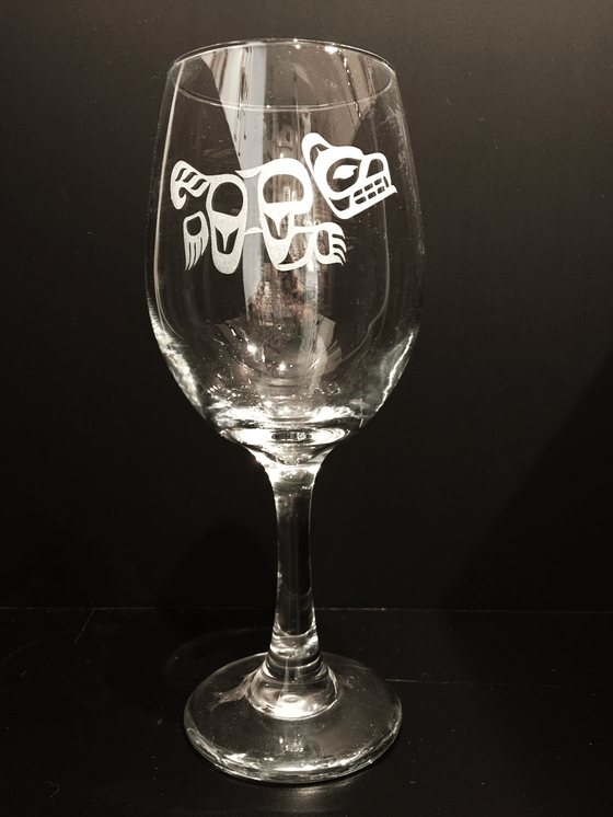 A long stem wine glass etched with a Haida wolf design. The wolf runs left to right at full speed, tail streaming behind it. The etching renders the wolf in frosted white against the clear glass.