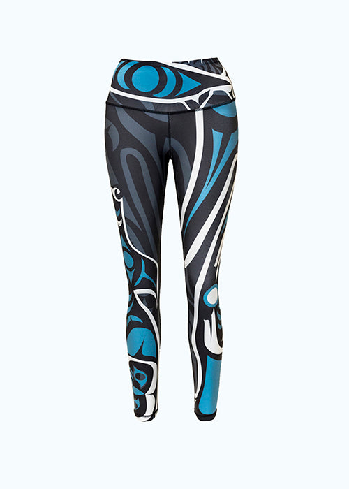 These black, teal, and white leggings are decorated with Coastal Salish wolf and moon, though they are hard to see in this photo. A teal eye shape is visible on the waist. There are flowing white and teal stripes on the left leg. The wolf faces up the right leg, and the top of its head can be seen in this photo.