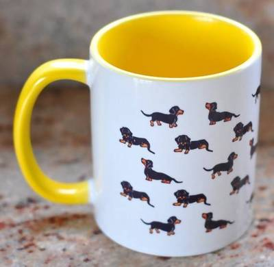 White mug with repeating Dachshunds and yellow handle