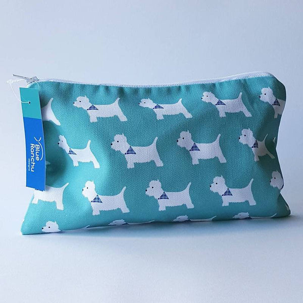 Blue makeup bag with repeating patterns of white westie dogs with blue neckerchiefs
