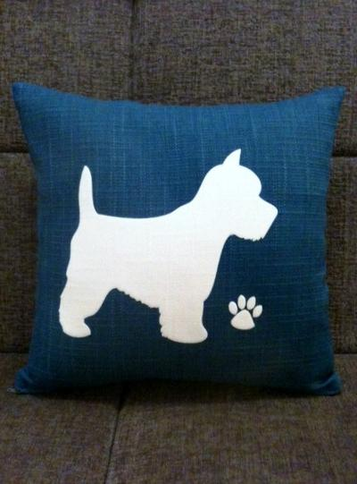 Blue cushion with white wesite and white pawprint