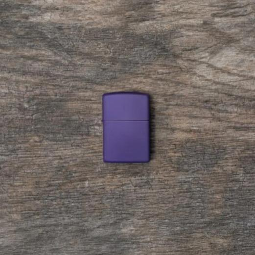 Lifestyle image of Purple Matte windproof lighter laying flat on a wooden surface