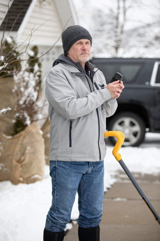 Man shoveling snow with the Black 12-Hour Refillable Hand Warmer in his hand