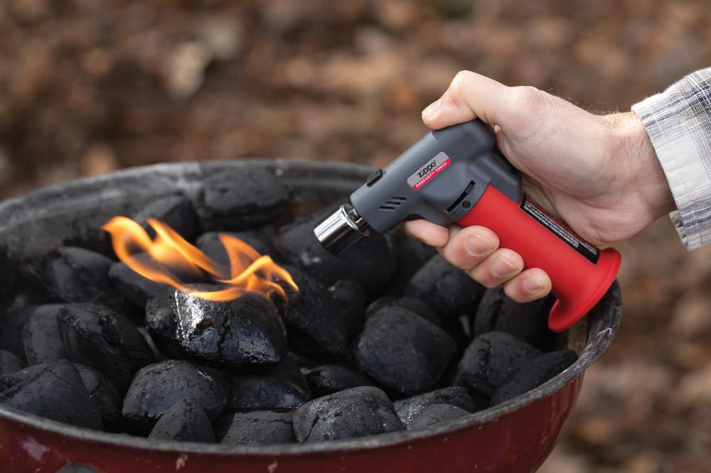 Lifestyle image of FireFast™ Torch lighting a charcoal grill