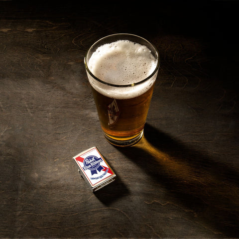 Lifestyle image of Pabst Blue Ribbon windproof lighter with beer