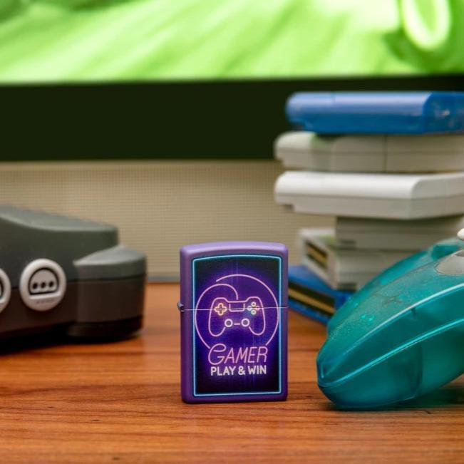 Lifestyle image of Gamer Design Purple Matte windproof lighter standing in front of Nintendo N64 system and gaming controller