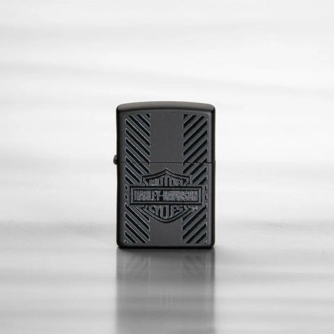 Lifestyle image of Harley-Davidson® Classic Logo Black Matte Windproof Lighter, standing on a sheet of reflective metal