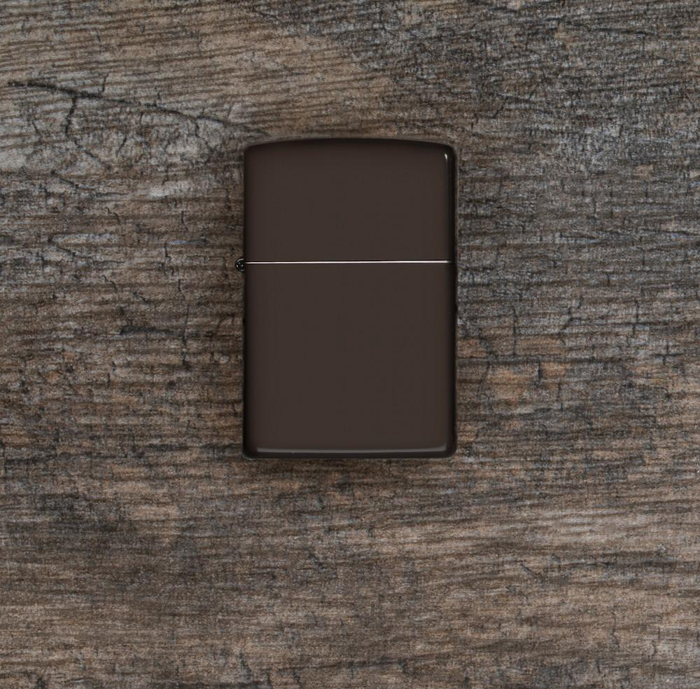 Lifestyle image of Brown Windproof Lighter laying flat on a wooden surface