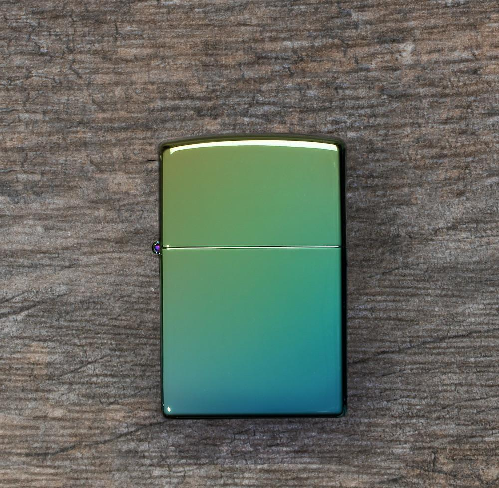 Lifestyle image of High Polish Teal Windproof Lighter laying flat on a wooden surface