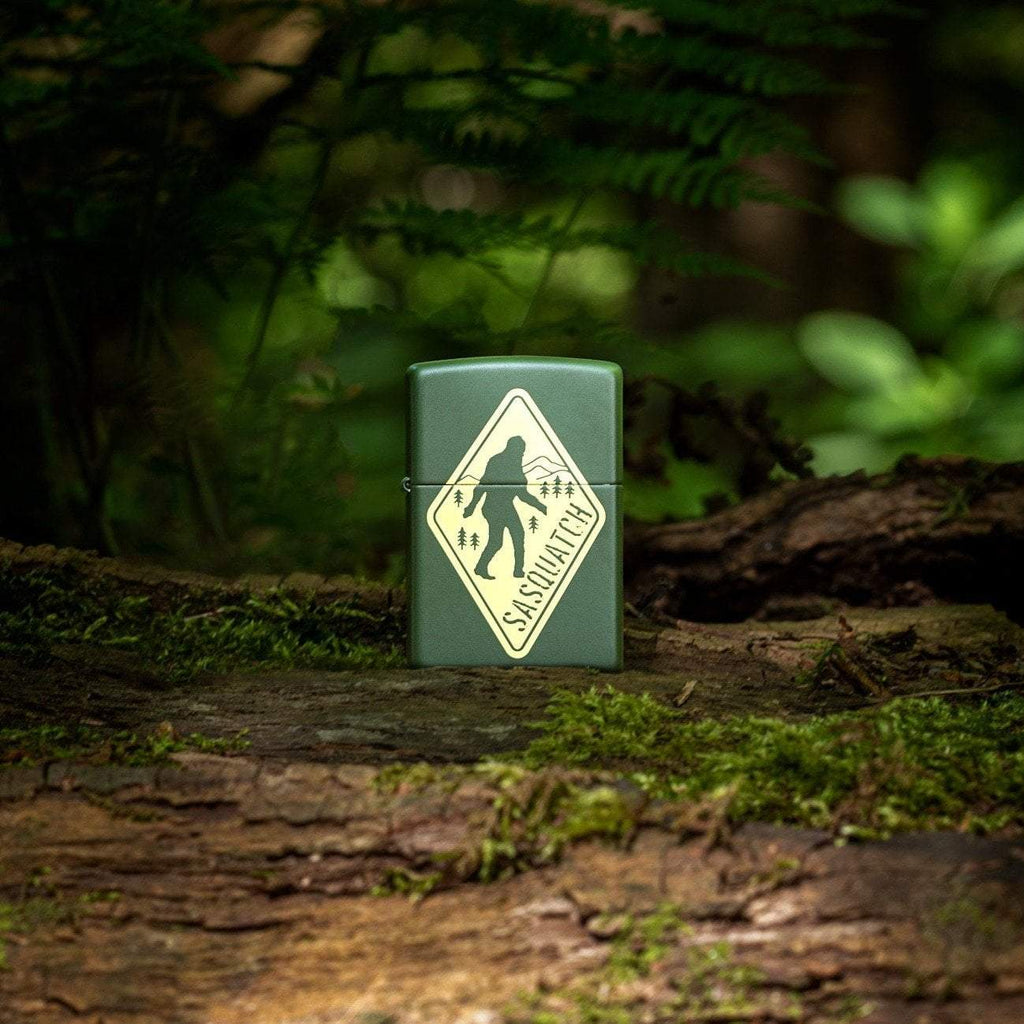Lifestyle image of Sasquatch Crossing Windproof Lighter standing in the woods on a log