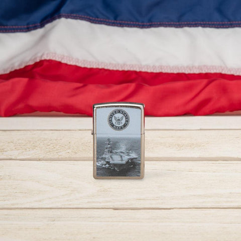 Lifestyle image of U.S. Navy® Aircraft Carrier Street Chrome™ Windproof Lighter standing on a wooden surface with the American Flag in the background