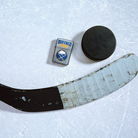 Lifestyle image of the NHL® Buffalo Sabres® Street Chrome™ Windproof Lighter laying on ice with a hockey puck and stick