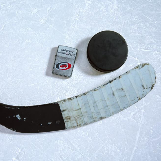 Lifestyle image of the NHL® Anaheim Ducks® Street Chrome™ Windproof Lighter laying on ice with a hockey puck and stick