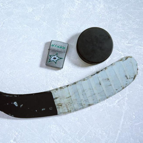 Lifestyle image of the NHL® Dallas Stars™ Street Chrome™ Windproof Lighter laying on ice with a hockey puck and stick