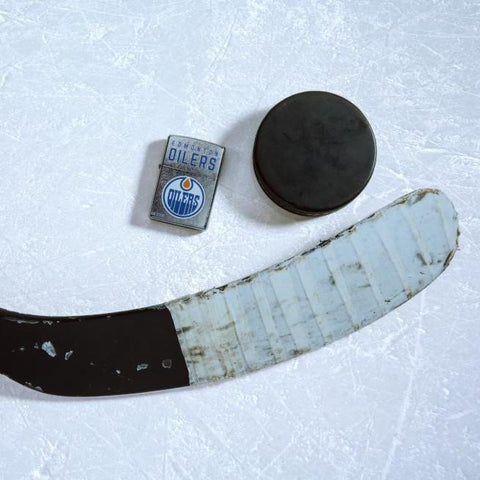 Lifestyle image of the NHL® Edmonton Oilers® Street Chrome™ Windproof Lighter laying on ice with a hockey puck and stick
