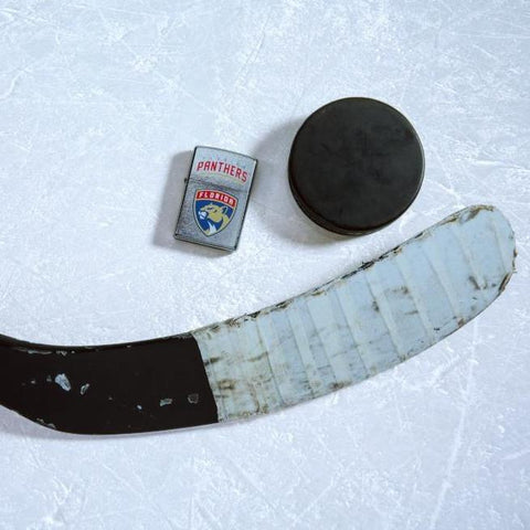 Lifestyle image of the NHL® Florida Panthers® Street Chrome™ Windproof Lighter laying on ice with a hockey puck and stick