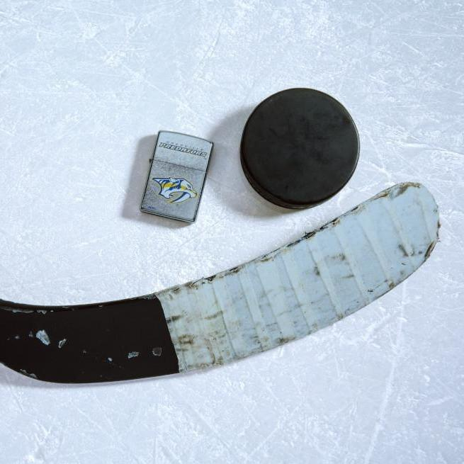 Lifestyle image of the NHL® Nashville Predators® Street Chrome™ Windproof Lighter laying on ice with a hockey puck and stick