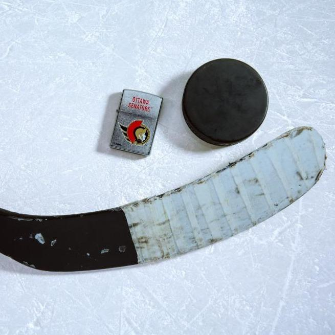 Lifestyle image of the NHL® Ottawa Senators® Street Chrome™ Windproof Lighter laying on ice with a hockey puck and stick