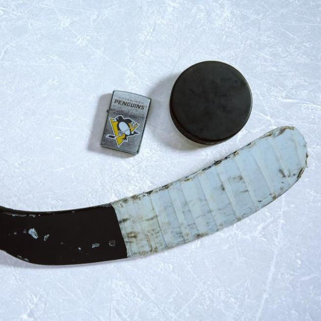 Lifestyle image of the NHL® Pittsburgh Penguins® Street Chrome™ Windproof Lighter laying on ice with a hockey puck and stick