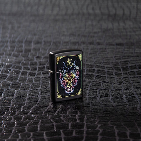 Lifestyle image of Neon Dragon Design Black Matte Windproof Lighter standing on a black scale textured surface