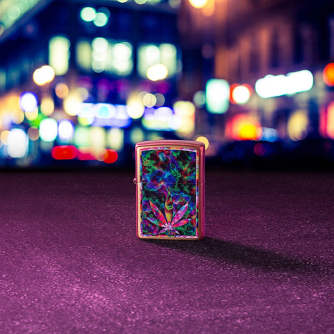 Lifestyle image of Leaf Design Brushed Brass Windproof Lighter standing in the street, with city lights out of focus in the background