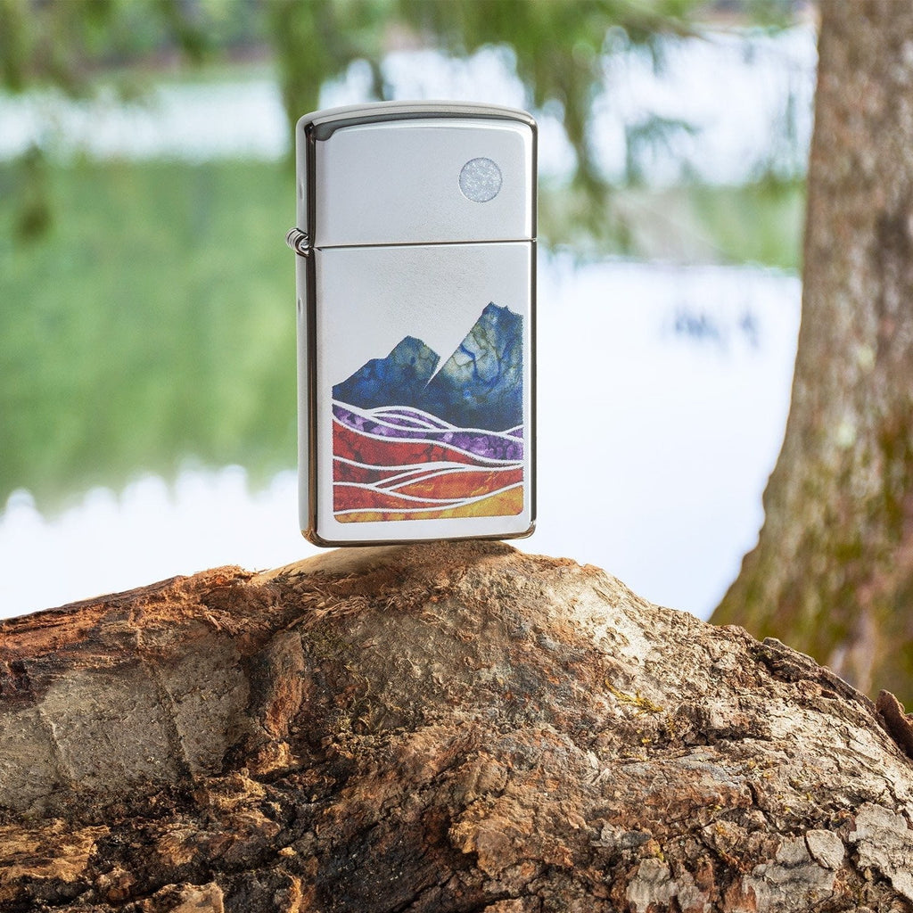 Lifestyle image of Slim® Landscape Design High Polish Chrome Windproof Lighter standing on a log in a forest.