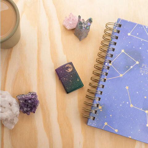 Lifestyle image of Starry Sky Design Iridescent Windproof Lighter laying flat on a desk with crystals and a sky themed planner