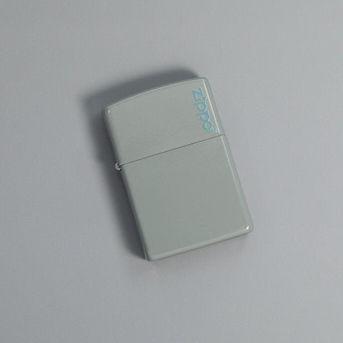 Lifestyle image of Classic Flat Grey Zippo Logo Windproof Lighter laying on a grey surface