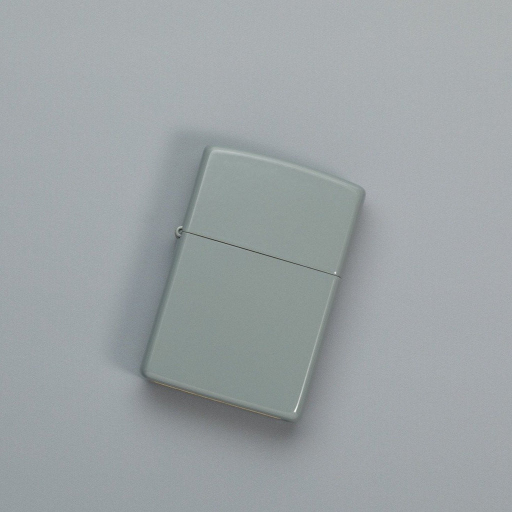 Lifestyle image of Flat Grey Windproof Lighter laying on a grey surface
